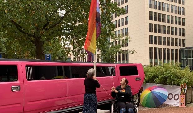 Ervaringsdeskundige Judith (rechts) en Ageeth Ouwehand hijsen de regenboogvlag.