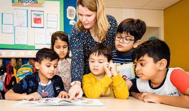 <p>Een juf leest met een aantal kinderen, die afkomstig zijn uit alle hoeken van de wereld.&nbsp;</p>