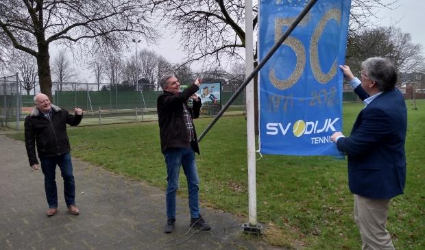 <p>Voorzitter Reinout van Elst hijst de jubileumvlag onder toeziend oog van Arnold Wagemakers (links) van het Sporthuis en wethouder Jocko Rensen.</p>