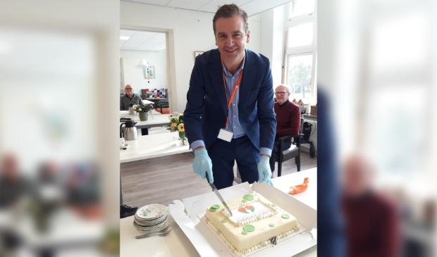 Bestuurder Cedric van der Meulen snijdt de taart aan op ontmoetingscentrum Pleinhart, gevestigd in Plein1 in Heemstede