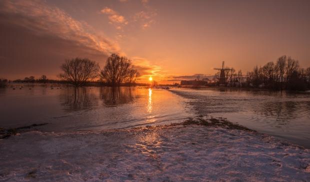 <p>Zonsondergang met sneeuw, ijs en een volstromende Woelse Waard met Gorinchem op de achtergrond</p>