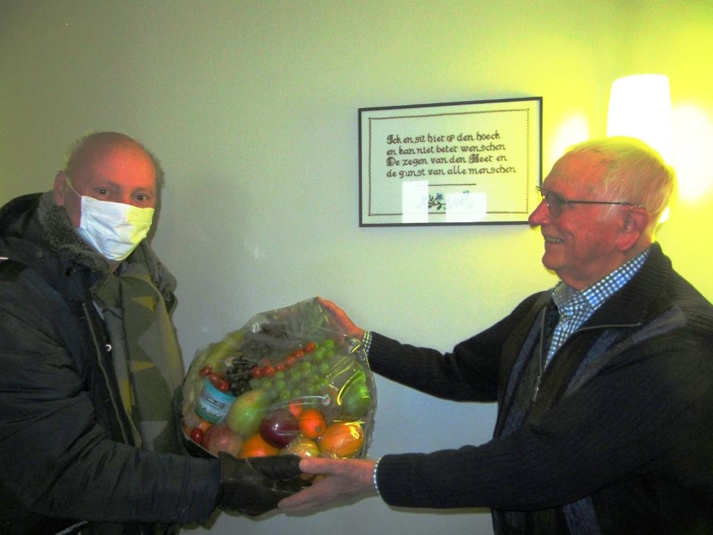 <p>Peter Bons, links op de foto, voorzitter van de Historische Vereniging Sliedrecht, biedt Jan van der Vlies een fruitmand aan.</p> <p>Sliedrechts Dialect</p> © BDU media