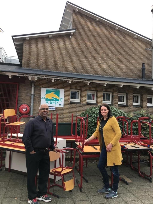 Voorzitter Sham Hira van SSCAZ neemt het schoolmeubilair in ontvangst uit handen van Vera van der Pol van OBS de Dolfijn Tessel Huizinga © BDU media