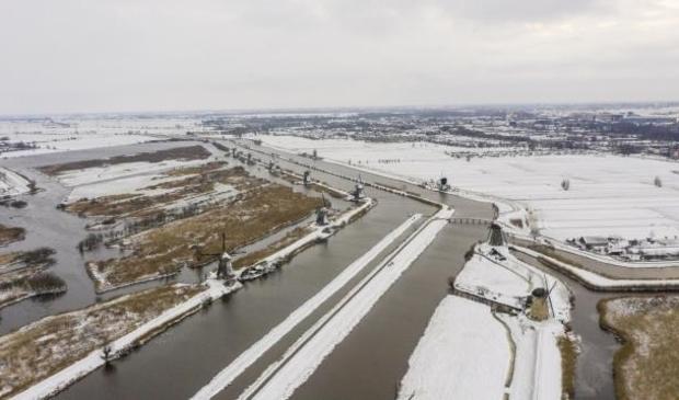 Sneeuw en ijs bij de molens van Kinderdijk in de Alblasserwaard, met links de Hoge Boezem van de Overwaard en rechts Alblasserdam.