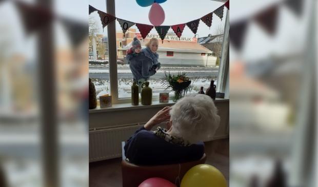Oma zwaait naar bezoekers buiten