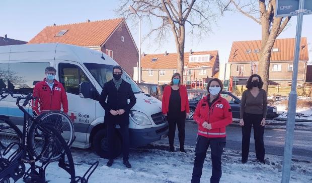 Burgemeester Tjapko Poppens met medewerkers van het Rode Kruis bij een van de bussen van de organisatie.