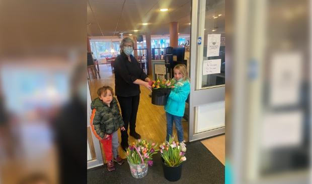 Sterre overhandigt de bloemen aan een medewerkster van Sparrenheide. Links op de foto haar broertje Jan.