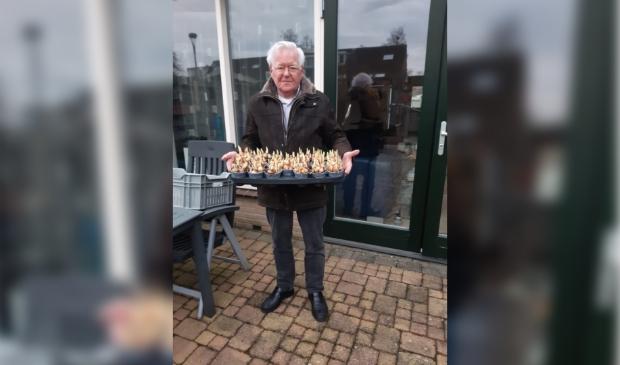 Vrijwilliger Jan Kamerman krijgt bakjes met narcissen om te bezorgen bij gasten van de Zonnebloem