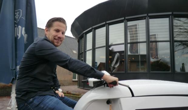 Peter zittend op een elektrische bakscooter voor de serre van Concordia Hoogland.