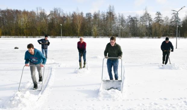 <p>Met man en macht wordt de ijsbaan sneeuwvrij gemaakt, zodat het ijs sneller kan aangroeien.</p>