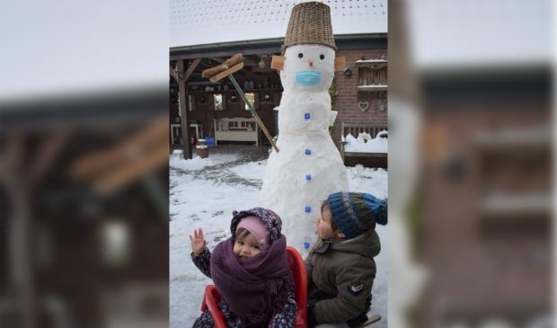 Ezra en Salomé hebben met opa een sneeuwpop gemaakt. Alles Corona-proof!