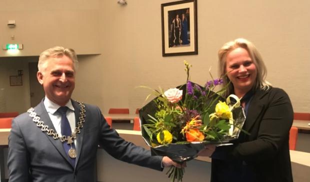 <p>Marcella van Esterik ontving direct na haar installatie als raadsgriffier bloemen uit handen van burgemeester Rob Metz.</p>