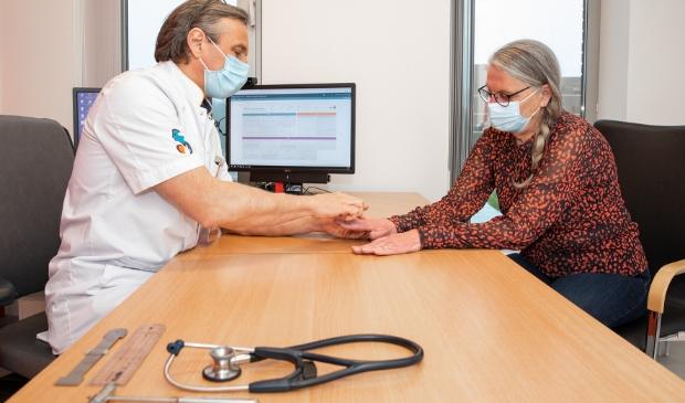 <p><strong>Reumatoloog Ilja Tchetverikov bekijkt met Klarie Stigter, de achthonderdste onderzoeksdeelneemster, de gevolgen van artritis psoriatica in haar handen.</strong></p>