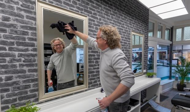 <p>Willem den Bleeker checkt of alles goed schoon is in de kapsalons alvorens hij woensdag weer open gaat</p>