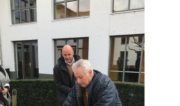 Felix Buijs bevestigt het plaatje van Meerwinkel op het bankje onder toeziend oog van Olivier Bongers