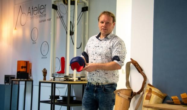 Jos Dölle houdt een redressiehelm vast, gemaakt met een 3D-printer.