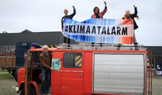De initiatiefnemers van het Klimaatalarm Amersfoort: in de deur Hans van Dijk (Grootouders voor het Klimaat) en op de auto van links naar rechts Laurens van Hofslot (Dwars), Fieke Westland (Fridays fot Future) en Ronja Breuk (Extinction Rebellion).
