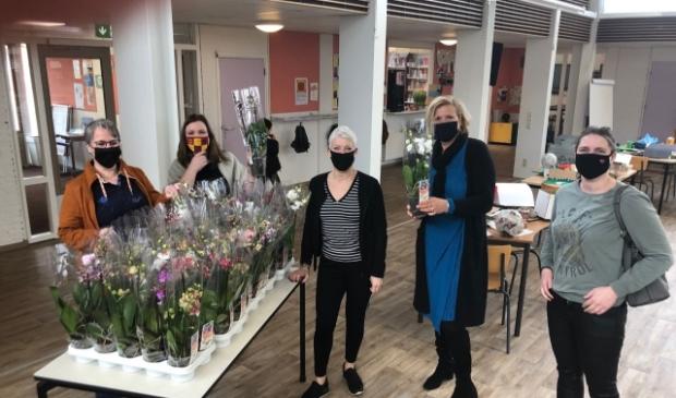 Leraren van basischool Klimop ontvangen de orchideeën.