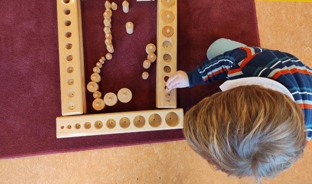 Leerling oefent met cilinderblokken (Montessorimateriaal)