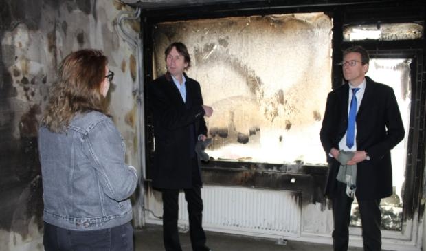 <p>Wethouder Herbert Raat en burgemeester Tjapko Poppens in de door de brand getroffen studentenwoning.</p>