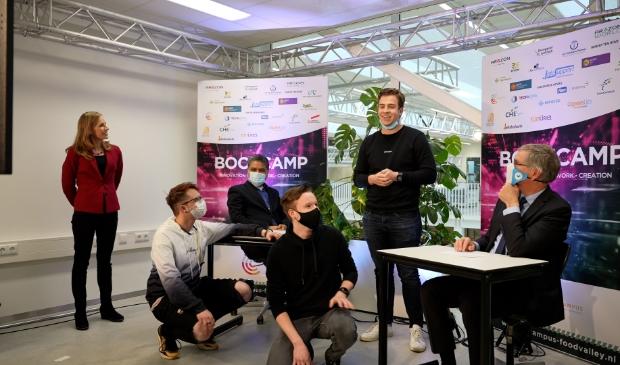 <p>Winnende studenten van &lsquo;Team 18&rsquo;, (links) Marlous Ten Kate, dagvoorzitter, (links achter bureau) Manish Dixit, opgavemanager Informatiesamenleving gemeente Veenendaal en (rechts achter bureau) Marco Verloop, wethouder gemeente Veenendaal.</p>