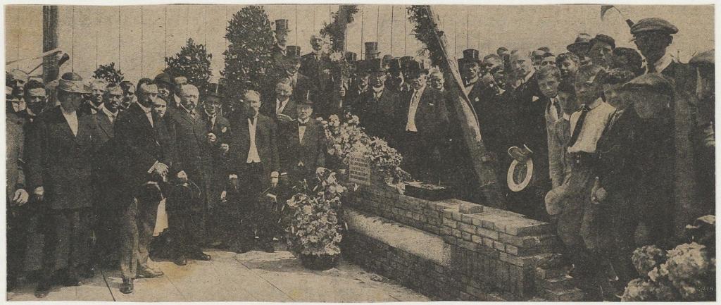 Eerste steenlegging voor de M.T.S. door H.J.Geyl,voorzitter van de T.S. De heer Geyl staat op de foto in het midden bij de bloemen. Achter de steen staat de Inspecteur van Onderwijs de Groot. Eigen Foto © BDU media