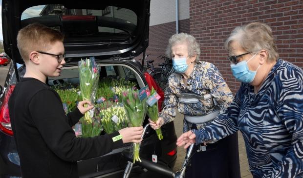 <p>Milan du Bois overhandigt tulpen aan bewoners van woonzorgcomplex De Samaritaan.</p>