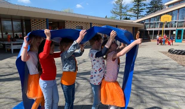 Leerlingen van de Koepelschool spelen spelletjes op het schoolplein