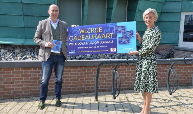 Henk Drok (KlantenSpaarPas) overhandigt de eerste Wijkse cadeaukaart aan burgemeester Iris Meerts