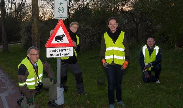 <p>Ook de burgemeester (links) en de wethouder (tweede van links) helpen mee de padden over te zetten</p>