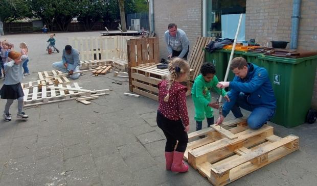 Kleuters van de Koepelschool maken onder leiding van vier handige vaders een modderkeuken en een loungebank
