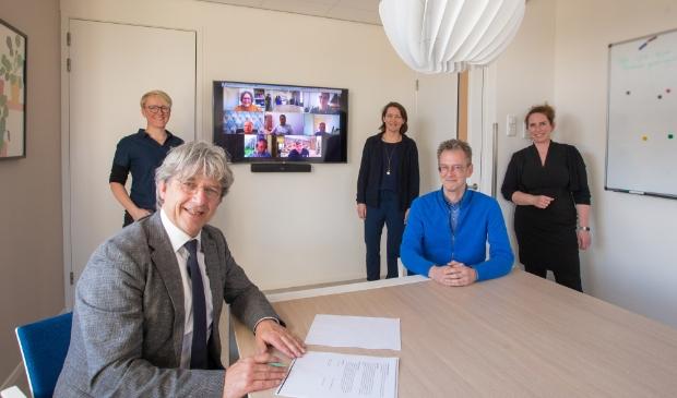 Wethouder Bert Koops en voorzitter van de huisartsengroep Dider Vermaas ondertekenen de intentieverklaring. Achteraan van links naar rechts huisartsen Ineke Weenink, Anouk Bettman en Marieke de Vries en de online aanwezige huisartsen.