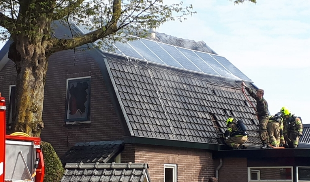<p>Terwijl net gearriveerde brandweerlieden dakpannen verwijderen, houdt een militair met een tuinslang het dak nat.</p>