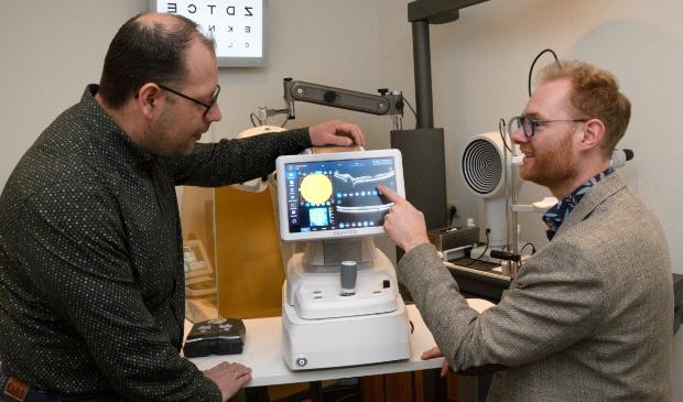 <p>Opticien Aris van den Berg (links) en optometrist Christian de Lijster bij de nieuwe OCT-netvliesscan.</p>