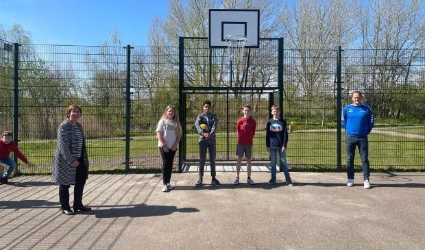 <p>Wethouder Dekker (links), Jasper Oele (rechts) en tussen hen in Dominique, Jayden, Wieger en Seth, bij de opening van het basketbalveld in Odijk</p>