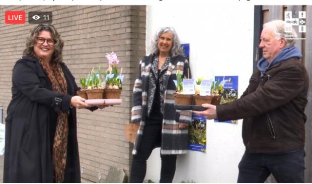 <p>Bewoner van in Overbos Jan Havenaar krijgt van wethouder Steffens enkele plantjes voor zijn geveltuin. NMCX-directeur Arjanne Lagendijk kijkt toe. &nbsp;</p>
