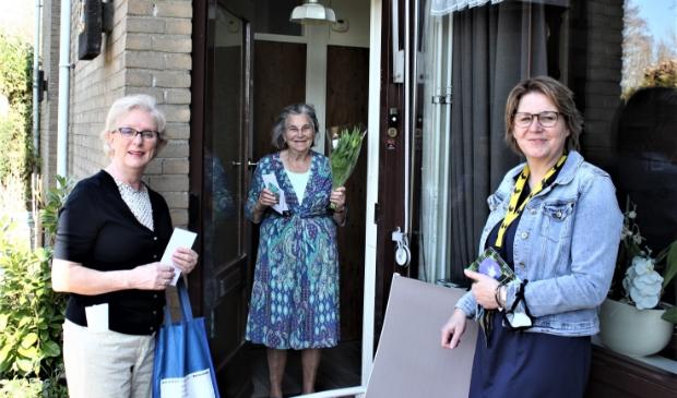 Jeanine Schaling van de Coalitie Erbij Woudenberg brengt samen met wethouder bloemen naar bezoekers van Samen op Zondagbren