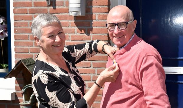 <p>Echtgenote Ria speldt de versierselen op bij Jaap van den Broek, zojuist benoemd tot Lid in de Orde van Oranje Nassau.</p>