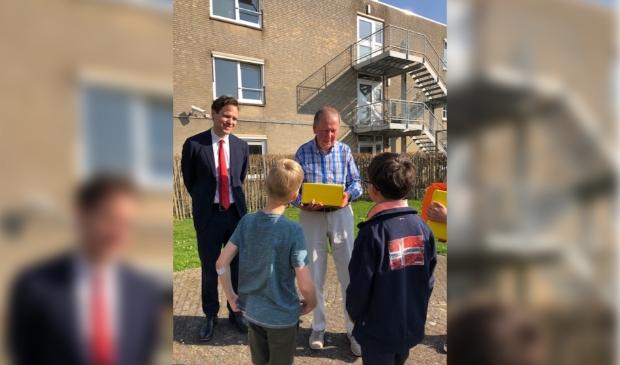 2 leerlingen van de Roelof Venemaschool overhandigen samen met Wethouder Van Ballegooijen een pakketje aan een 88-jarige bewoner van Nieuw Vredenhoven