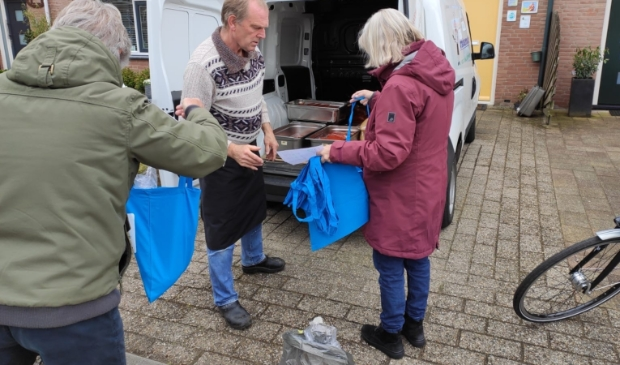Traiteur Nol verdeelt de soepen onder de vrijwilligers