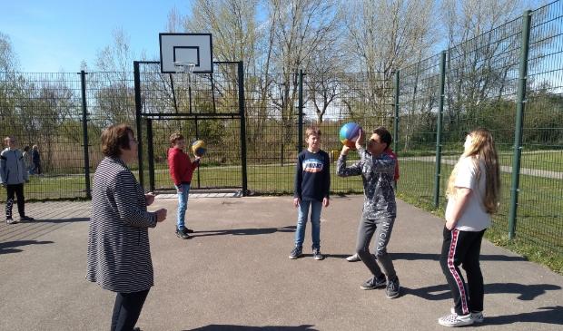 Wethouder Ali Dekker krijgt basketbaltraining van Jayden (11).  Agnes Corbeij © BDU media