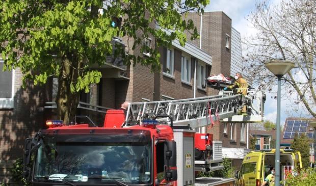 Brandweer hijst vrouw haar woning binnen.