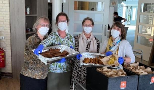 <p>Medewerkers van Zorgcentrum Elim tonen de bijzondere warme maaltijd die de bewoners woensdagmiddag kregen.&nbsp;</p>
