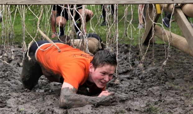 Eén van de bijna 5000 deelnemers ploeterend door de modder van recreatiegebied De Groene Weelde.