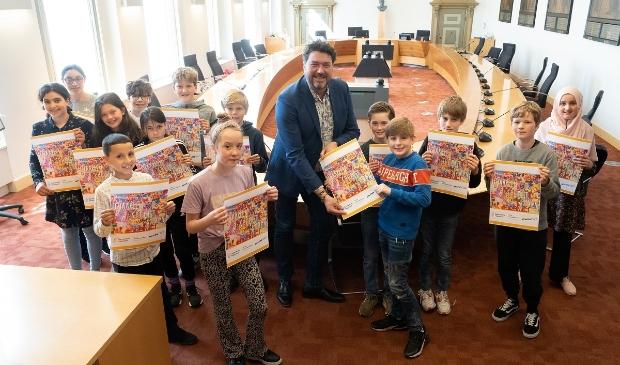 <p>De kinderraad biedt hun anti-discriminatieposter aan wethouder Jur Botter aan.</p>