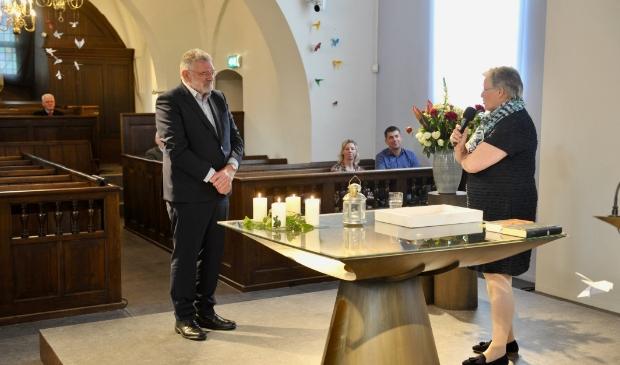 Ida Hogendoorn spreekt de jubilerende organist Frank Firet toe.