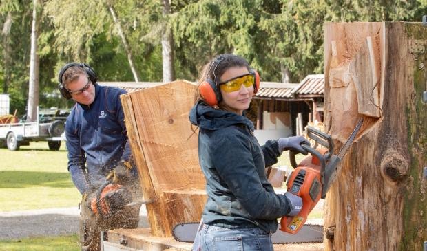Claartje Boot en Dave Harmsworth druk met zagen van sculpturen uit een boomstam. De kunstwerken komen op het Midget Golf park in Lage Vuursche te staan.