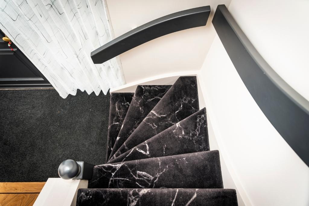 De trap is bedekt met zwart tapijt, voorzien van een marmerachtige print. Pauw Media © BDU media