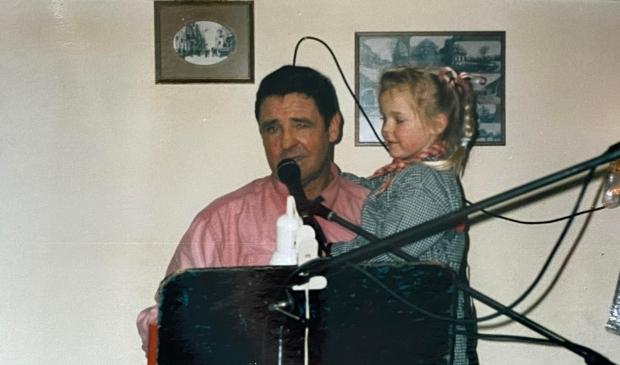 """Een jonge Tiffany Perrier-Plugers met haar opa, Jacky van Dam. ,,Tijdens optredens mocht ik altijd op zijn schoot zitten."""" Familiefoto © BDU Media"""