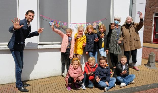 <p>Wethouder Kraaijeveld (links) samen met kinderen van de Jenaplanschool, initiatiefneemster van de zwaaistickers Tineke Advokaat (met mondkapje) en een van de bewoners van verpleeghuis Molenhoek (geheel rechts)</p>